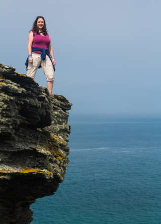 south west england: Female hiker stands on cliff edge near the South West Coast Path at Tintagel, Cornwall, England, UK