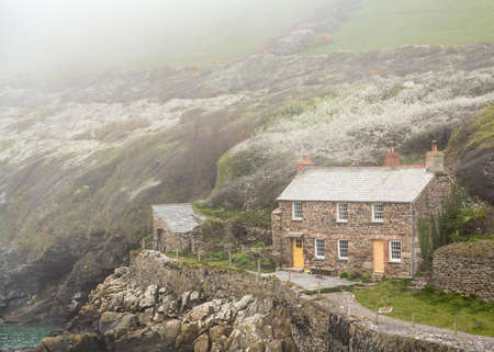 mists: View of stone cottage and hillside as the mists roll in over the ocean in Port Quin, Cornwall, England, UK