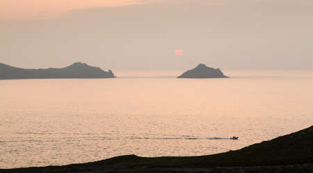 quin: Small boat races back to port by headland overlooking the coast at sunset at Port Quin, Cornwall, England, United Kingdom Stock Photo