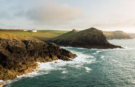 quin: Doyden Castle on headland and whitewashed house on wide panorama of coastline at Port Quin, Cornwall, England, United Kingdom Editorial