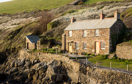 quin: View of stone cottage and hillside in late evening sunlight in Port Quin, Cornwall, England, UK Editorial