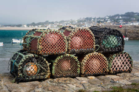 lobster pot: Rope and wooden frame lobster pot or trap stacked on stone wall of harbor on south coast of England