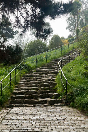 Large rocks forming difficult pathway up hillside on stony steps into fog covered distance