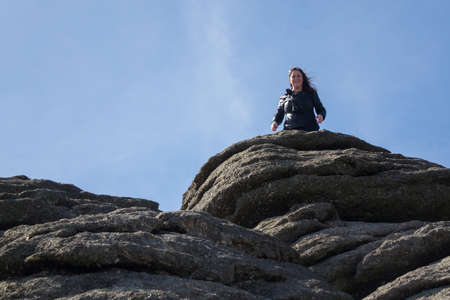 british ethnicity: Haytor or Hay Tor rocks with single female hiker on the top of the granite rock on Dartmoor, Devon, England, United Kingdom Stock Photo