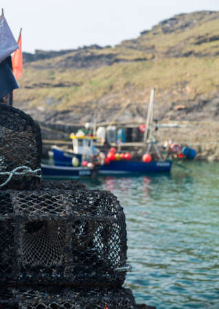 lobster pot: Rope and wooden frame lobster pot or trap stacked on stone wall of harbor in Boscastle, Cornwall, England UK