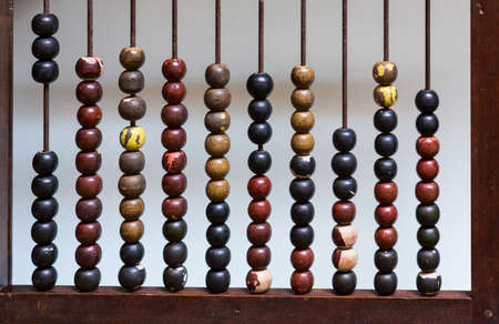 sums: Vertical view of abacus with painted wooden beads arranged to count out calculations Stock Photo