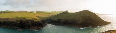 headland: Doyden Castle on headland and whitewashed house on wide panorama of coastline at Port Quin, Cornwall, England, United Kingdom Editorial