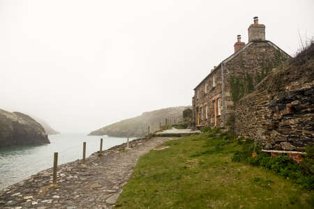 quin: View of harbour or harbor as the mists roll in over the ocean in Port Quin, Cornwall, England, UK