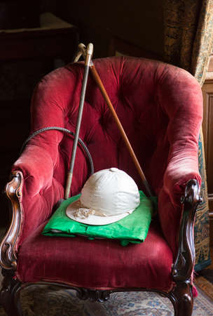 red velvet: Old horse riding silks and hat with whip and stick on red velvet chair in window light