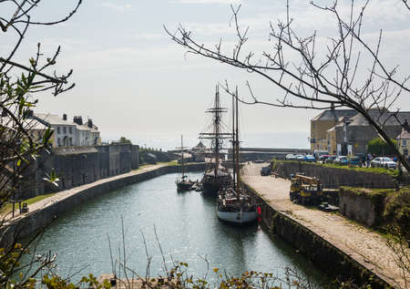 harbour: Harbour or harbor with two sailing ships in the dock area and looking out to sea in Charlestown, Cornwall, England, UK