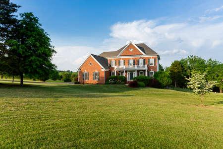 家や大規模な現代米国住宅暖かい日当たりの良い夏の日に芝生と庭園のガレージの前