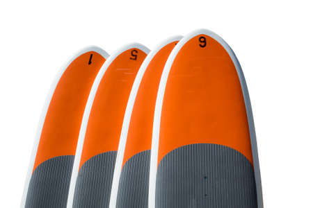 sporting equipment: Row of four upright standup paddle boards or body boards, surf boards isolated against white background
