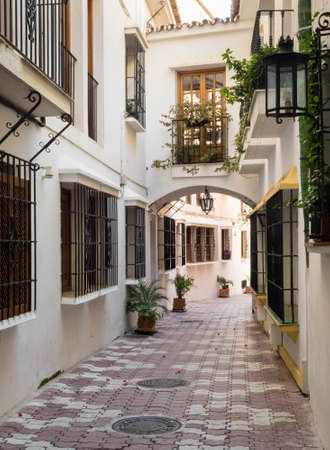 flower pot: Narrow street with white homes and window grilles in Marbella, Andalucia, Spain Stock Photo