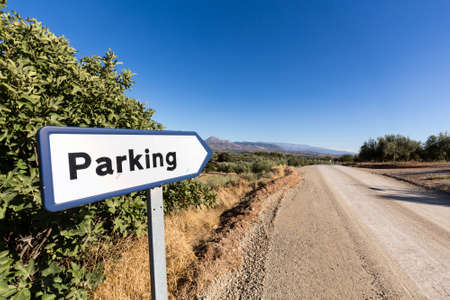 humour: Parking road sign by side of dry dusty road with olive trees and mountains in the distance