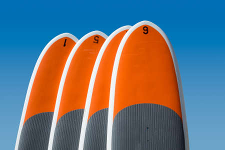 upright row: Row of four upright standup paddle boards or body boards, surf boards against deep blue sky