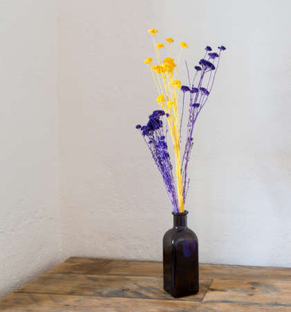 flores secas: Flores púrpuras y amarillas secas en botella azul como un florero en una vieja mesa de madera o un banco