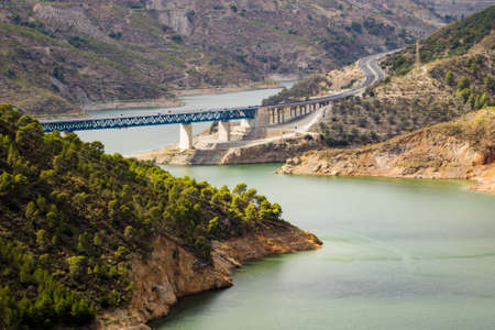 europe travel: autoroute or motorway crosses Rules Reservoir and RIo Guadalfeo as it runs north through Sierra Nevada Mountains in Andalucia, Spain Stock Photo