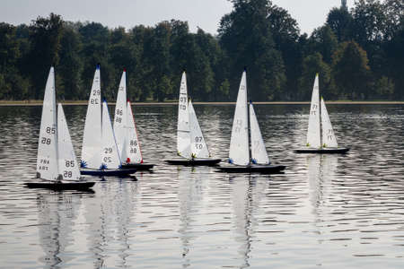 minature: Model yachts or boats race across Round Pond in Kensington Gardens, London, England Stock Photo