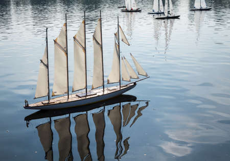 multi race: Model yacht with many sailes races across Round Pond in Kensington Gardens, London, England