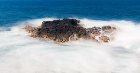 Strong waves and swell flow over lava rock off Queens Bath near Princeville, Kauai