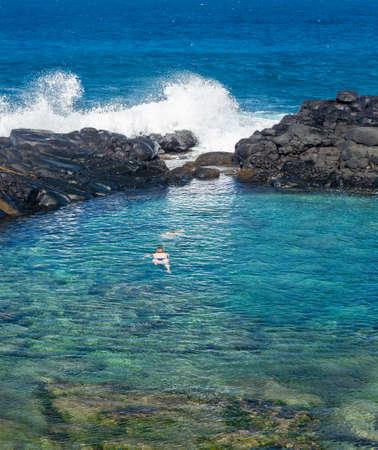 kauai: Snorkeling swimmer in Queens Bath near Princeville, Kauai
