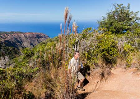 ocean state: Senior male hiker on Awa`awapuhi trail from Kokee State Park to Na Pali coast  overlooking Pacific ocean in Kauai, Hawaii, USA