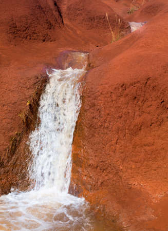 waimea canyon state park: Small waterfall in stream causing erosion into red rocks near the Grand Canyon of the Pacific or Waimea Canyon on island of Kauai in the Hawaiian islands Stock Photo