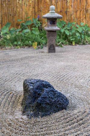 raked: Large lava rock anchors the Japanese raked stone Zen garden with lantern and bamboo fence in Kauai, Hawaii Stock Photo