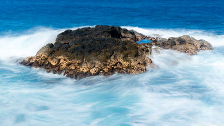 swell: Strong waves and swell flow over lava rock off Queens Bath near Princeville, Kauai