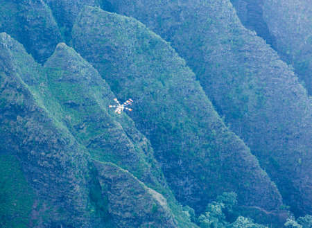 end of the trail: Helicopter on flight over Na Pali coast taken from end of Awa`awapuhi trail at Nualolo Valley overlooking Pacific ocean in Kauai, Hawaii, USA Stock Photo