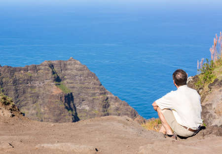 ocean state: Climber on edge of Awa`awapuhi trail from Kokee State Park to Na Pali coast ends at Nualolo Valley overlooking Pacific ocean in Kauai, Hawaii, USA