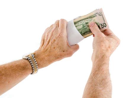cash money: Pila de cincuenta y veinte billetes de dólar estadounidense que se puso en el sobre por manos caucásicos de edad como si ofreciendo como un regalo Foto de archivo