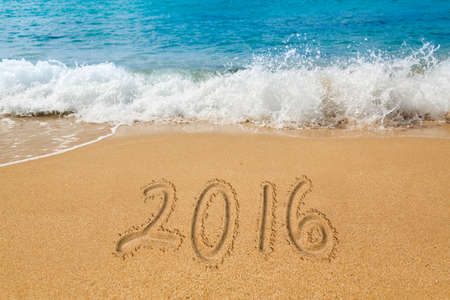 sand drawing: Sand drawing on warm beach by ocean surf in Caribbean spelling 2016 as an illustration of Happy New Year Stock Photo