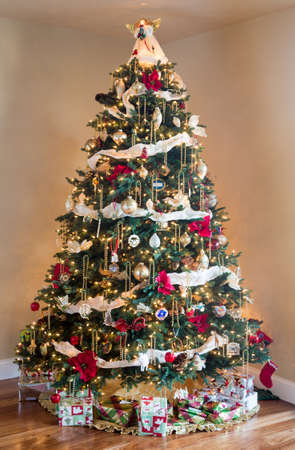ornately: Ornately decorated christmas tree in the corner of a modern living room with wrapped presents and gifts under the branches