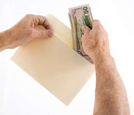 cash money: Pila de cincuenta y veinte billetes de un dólar de Estados Unidos está poniendo en el sobre por altos manos caucásicas como si ofrecer como regalo Foto de archivo