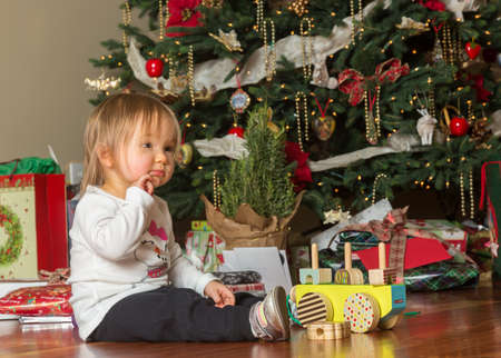thoughful: Young caucasian toddler sits in front of a Christmas tree opening gifts and toys  with a thoughful expression