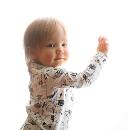 wistful: Isolated head and shoulders of caucasian ethnicity baby girl one year old facing the camera over her shoulder and leaning against a pure white background