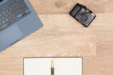 desk tidy: Tidy organized desk top with laptop, camera and notebook with pen on an oak wooden table for designer workspace Stock Photo