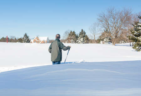 Senior man with snow shovel looking at snow drifts on driveway as he tries to dig out from the blizzard