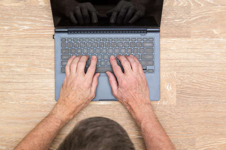 teleworker: Senior caucasian adult man typing on laptop keyboard on wooden desk in photo taken from above Stock Photo