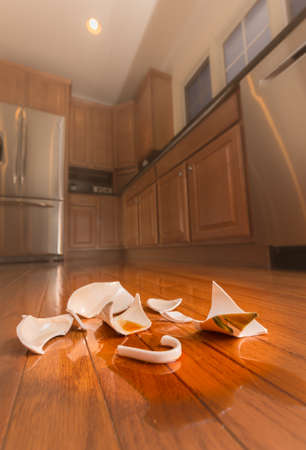 Concept of domestic disturbance at home with broken coffee cup on floor of modern kitchen Imagens