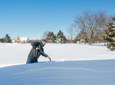 Senior man with snow shovel looking at snow drifts on driveway as he tries to dig out from the blizzard photo