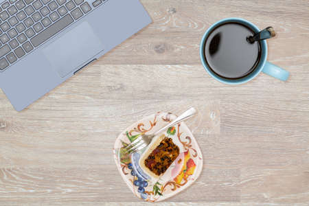desk tidy: Tidy organized desk top with laptop, cup of coffee and fruitcake on an oak wooden table for designer workspace