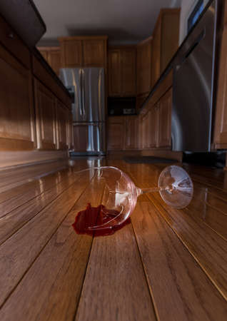 Concept of domestic disturbance at home with broken wine glass on floor of modern kitchen