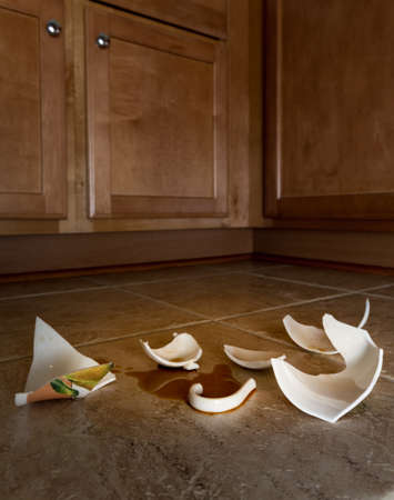 Concept of domestic disturbance at home with broken coffee cup on floor of modern kitchen Banco de Imagens - 51797527