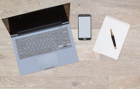 Tidy organized desk top with laptop, smartphone and notebook with pen on an oak wooden table for designer workspace or image for website page Stock Photo