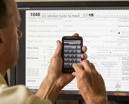 Electronic tax form 1040 for 2015 for US individual return on screen with smartphone calculator photo