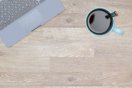 desk tidy: Tidy organized desk top with laptop and cup of coffee or tea on an oak wooden table for designer workspace Stock Photo