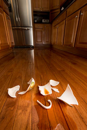 disturbance: Concept of domestic disturbance at home with broken coffee cup on floor of modern kitchen Stock Photo