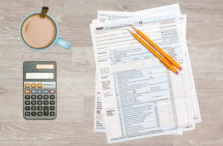 irs: USA IRS tax form 1040 for year 2015 with pencils and calculator with a cup of coffee on wooden desk and taken from above